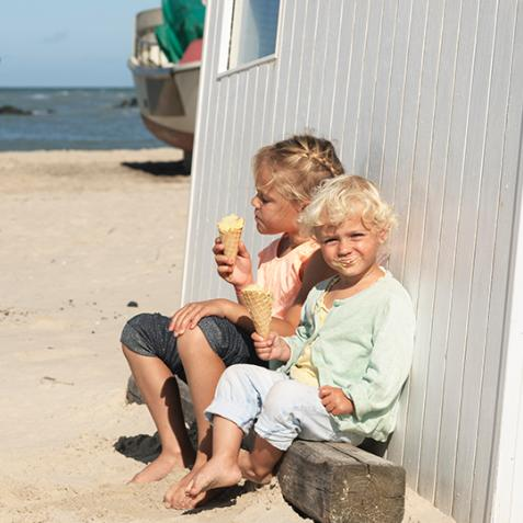 Barn som spiser is på stranden
